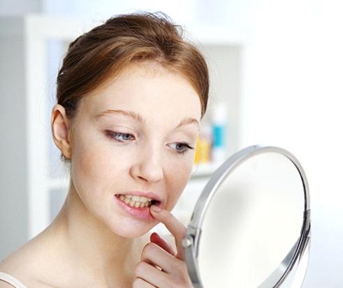 Woman Examining Teeth In Mirror